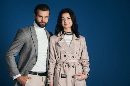 Photo pour Couple attractif permanent et regardant la caméra isolée sur bleu - image libre de droit