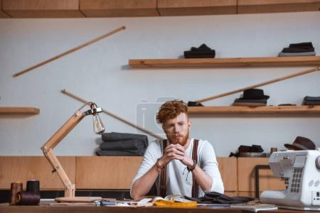 stylish young male fashion designer sitting at table at workplace