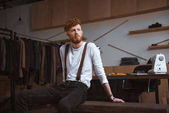 stylish young bearded fashion designer looking away in workshop