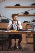 pensativo joven diseñador de moda masculina mirando de lejos mientras está sentado en el lugar de trabajo