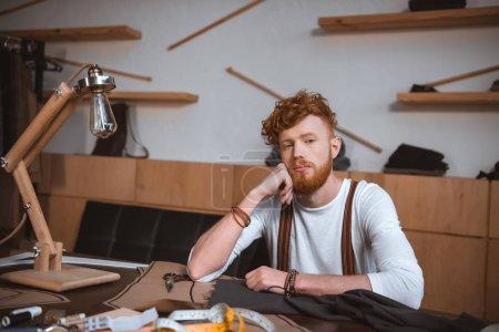 Photo pour Songeur élégant jeune styliste assis à table et en regardant la caméra - image libre de droit
