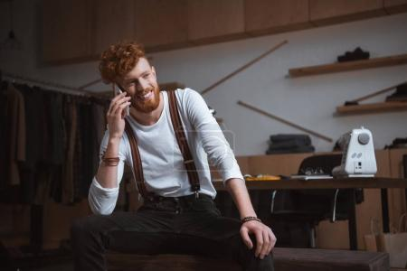 handsome young smiling fashion designer talking by smartphone at workplace