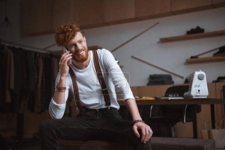 Foto de Guapo joven diseñador de moda sonriente hablando por teléfono inteligente en el lugar de trabajo - Imagen libre de derechos