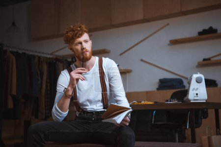 Photo for Pensive young male fashion designer looking away while taking notes in notebook at workplace - Royalty Free Image