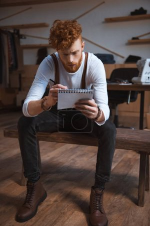 focused young male fashion designer taking notes in notepad at workplace