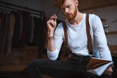 Foto de Diseñador de moda masculina joven pensativo con cuaderno y lápiz en lugar de trabajo - Imagen libre de derechos