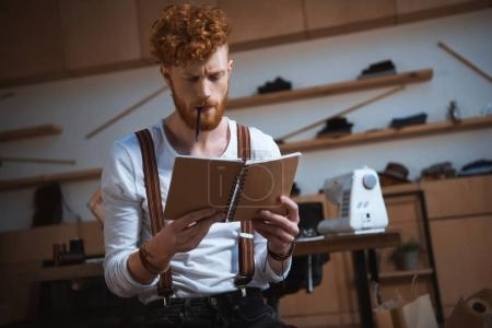 serious young male fashion designer holding notebook at workplace