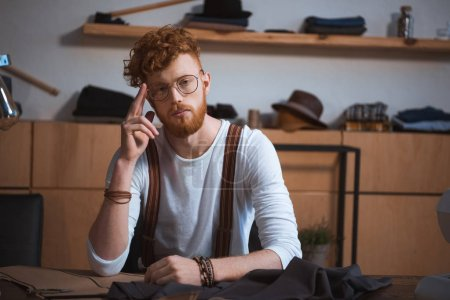 handsome young fashion designer in eyeglasses looking at camera while sitting at workplace