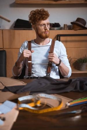 Photo for Pensive young bearded fashion designer in eyeglasses looking away while sitting at workplace - Royalty Free Image