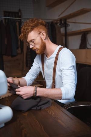 Photo pour Jeune designer de mode masculine en tenant le tissu à l'atelier de lunettes de vue - image libre de droit