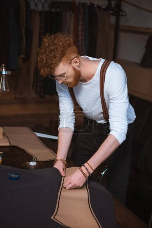 young male fashion designer in eyeglasses and suspenders working with sewing patterns