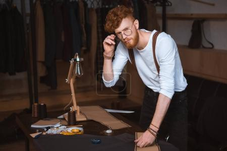 Photo for Young male fashion designer in eyeglasses looking at camera while working with sewing patterns and fabric - Royalty Free Image