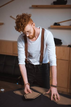 young male fashion designer in eyeglasses working with sewing patterns and fabric