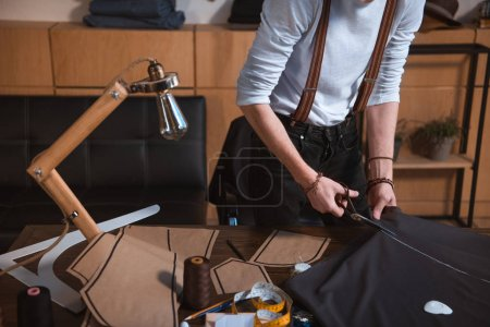 cropped shot of young male fashion designer working with scissors and fabric in workshop