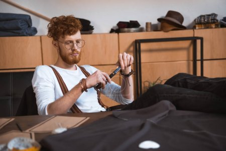young male fashion designer holding scissors while sitting at table with sewing patterns and fabric