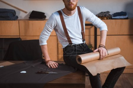 Photo for Cropped shot of young male fashion designer sitting on table with fabric and sewing tools at workshop - Royalty Free Image