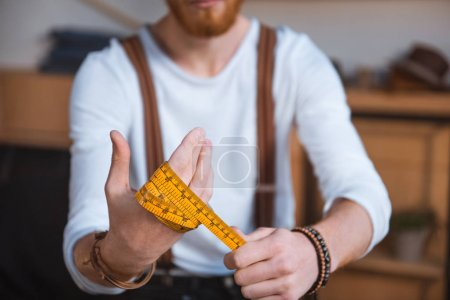close-up view of young male fashion designer holding measuring tape
