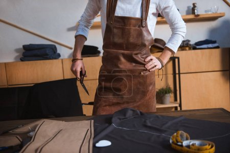 cropped shot of male fashion designer in apron working with sewing tools and fabric at workshop