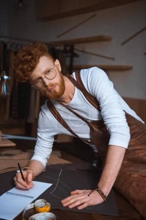 handsome young fashion designer in apron and eyeglasses taking notes in notebook