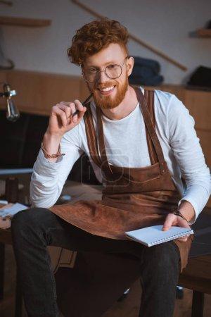 Foto de Guapo joven diseñador de moda en anteojos sosteniendo el lápiz con notebook y sonriendo a cámara - Imagen libre de derechos