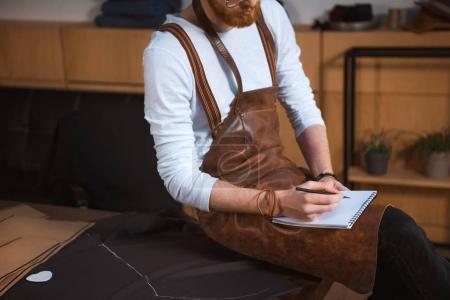 Foto de Recortar el tiro de diseñadores hombre barbudo en delantal tomando notas en el cuaderno - Imagen libre de derechos