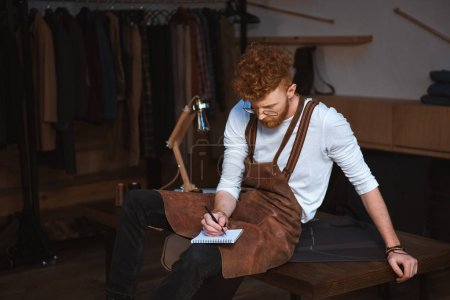 young male fashion designer in apron and eyeglasses taking notes in notebook