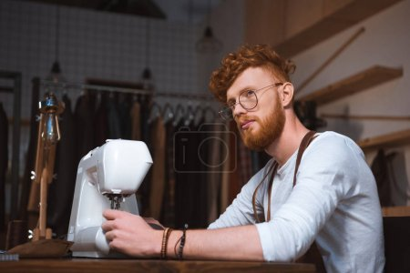 pensive young fashion designer working with sewing machine and looking away at workshop