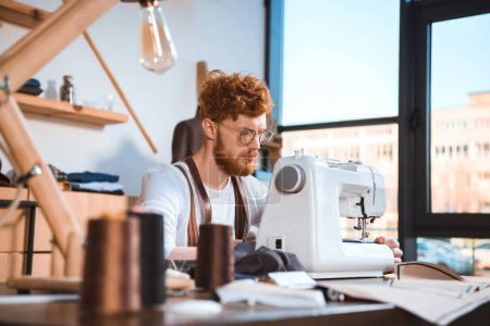 Photo for Focused young fashion designer in eyeglasses working with sewing machine at workshop - Royalty Free Image