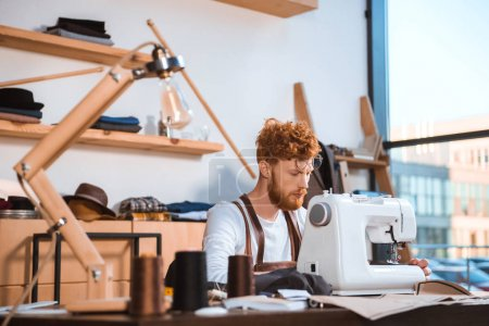 Photo for Bearded young fashion designer working with sewing machine at workshop - Royalty Free Image
