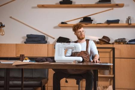 Photo for Handsome young fashion designer in eyeglasses looking away while working with sewing machine in workshop - Royalty Free Image