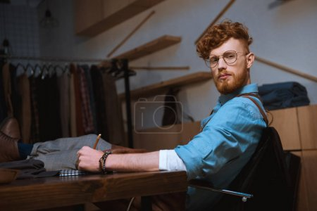 Photo for Young male fashion designer in eyeglasses looking at camera while taking notes at workplace - Royalty Free Image