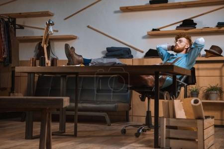 Photo pour Jeune designer de mode masculine en tablier et lunettes assis avec les mains derrière la tête au milieu de travail - image libre de droit