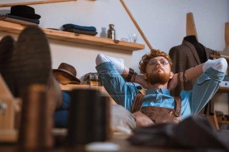 Foto de Enfoque selectivo de jóvenes diseñadores de moda masculina en delantal y anteojos sentado con las manos a la cabeza en el lugar de trabajo - Imagen libre de derechos