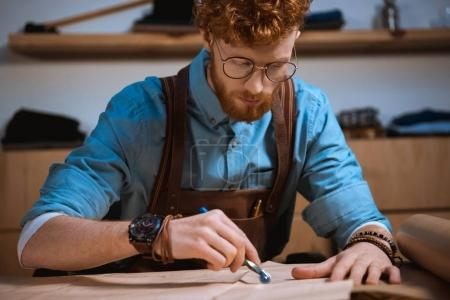 focused young male fashion designer in eyeglasses making sewing patterns at workplace