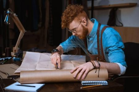 young male fashion designer in apron and eyeglasses making sewing patterns at workplace