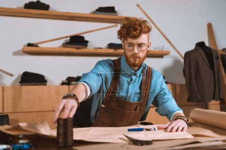 young male fashion designer in apron and eyeglasses sitting at workplace