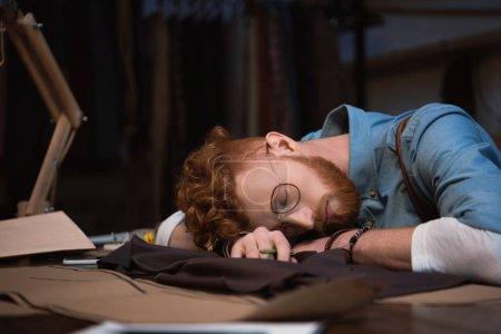 Photo pour Fatigué de jeune styliste en lunettes de couchage sur table au milieu de travail - image libre de droit
