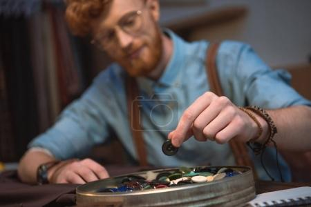 close-up view of young male fashion designer working with colorful buttons at workshop