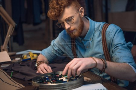 young male fashion designer in eyeglasses working with colorful buttons and fabric at workshop