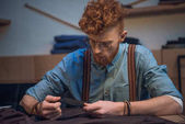young male fashion designer in eyeglasses working with fabric at table