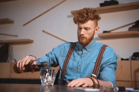 handsome stylish young man pouring whisky from bottle in glass