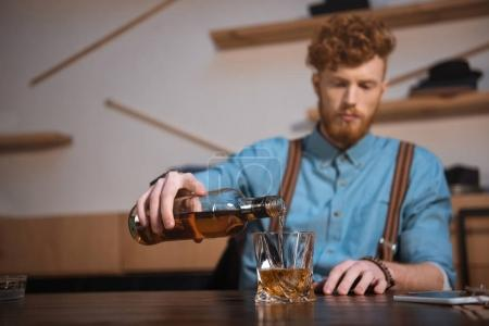 close-up view of young man pouring whisky from bottle in glass