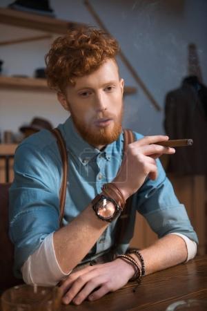 stylish young man smoking cigar at clothing design studio