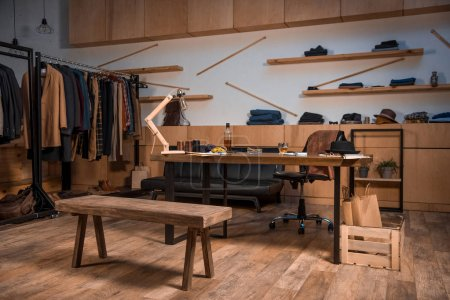 Photo for Clothing design studio interior with stylish clothes on hangers and bottle of whisky on table - Royalty Free Image