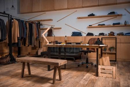 Photo pour Vêtements design studio intérieur avec style des vêtements sur cintres et bouteille de whisky sur la table - image libre de droit