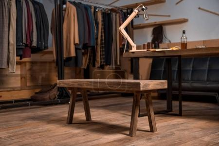 Photo pour Styliste au travail avec le style des vêtements sur cintres et bouteille de whisky sur la table - image libre de droit