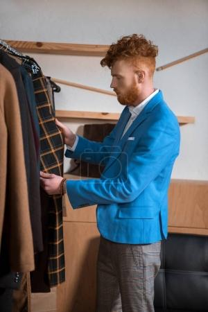 stylish young man in blue suit jacket choosing clothes in boutique