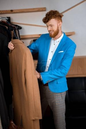 handsome smiling young man holding hanger with stylish brown overcoat in boutique