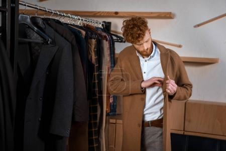handsome young man wearing brown overcoat in boutique