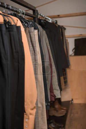 stylish male clothes on hangers in boutique